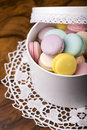 Pastel color macaroons in vintage round box on a wooden background Royalty Free Stock Image