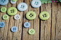 Pastel colored buttons differently sized on table in soft green and blue Stock Image