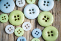 Pastel colored buttons differently sized on table in soft green and blue Stock Photos