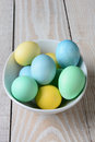 Pastel easter eggs in a bowl high angle view of the white is full of yellow green and blue dyed on rustic farmhouse Royalty Free Stock Image