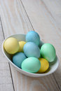 Pastel easter eggs in a bowl vertical high angle shot of of the white is full of yellow green and blue dyed on rustic Royalty Free Stock Photos