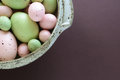 Pastel easter eggs hand crafted pink and green in speckled pottery bowl on aubergine background with room for your text Royalty Free Stock Photography