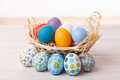 Pastel easter eggs painted on a bleached wooden table in a weaved basket Royalty Free Stock Photography