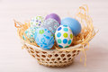 Pastel easter eggs painted on a bleached wooden table in a weaved basket Royalty Free Stock Images