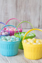 Pastel jelly beans in colored baskets for easter brightly Stock Photos
