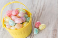 Pastel jelly beans in yellow basket many colored for easter Stock Image