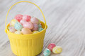 Pastel jelly beans in yellow basket many colored for easter Royalty Free Stock Image