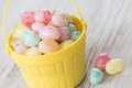 Pastel jelly beans in yellow basket many colored for easter Royalty Free Stock Images