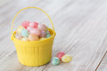 Pastel jelly beans in yellow basket many colored for easter Stock Photography