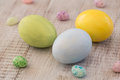 Pastel Painted Easter Eggs and Jelly Beans on White Wood Backgro