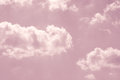 Pastel pink sky with white fluffy clouds