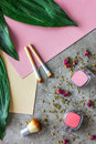 Pastel set of decorative cosmetics with brushes on stone woman desk background top view pattern