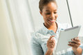Pastime copy spaced image of an attractive black woman with a tablet in hands on the foreground Royalty Free Stock Images