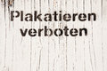 Pasting forbidden white wooden wall with text plakatieren verboten meaning in german Royalty Free Stock Photos
