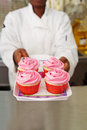 Pastry chef offering a tray of pink cupcakes Royalty Free Stock Photo
