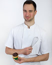Pastry chef on white background with a whisk in his hand and a cupcake in the other hand Royalty Free Stock Photos