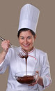 Pastry cook woman tasting chocolate funny cream Royalty Free Stock Images
