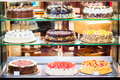 Pastry shop in glass cabinet display with selection of cream or fruit cake Royalty Free Stock Photo