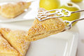 Pastry tongs holding apple turnover taking from a platter Stock Photography