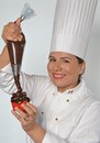 Pastry woman cook holding a chocolate whipped cream cone on chocolate cupcake Stock Photography
