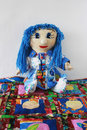 Patchwork doll blue hair sitting cheerful patchwork rug Stock Photos
