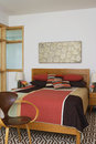 Patchwork quilt on bed by chair empty Stock Photography