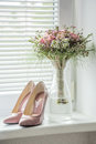 Patent pointed old pink pumps with matching flower bouquet Royalty Free Stock Photo