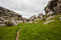 Path in the gravina landscape of a gorge italy these formations are known as with caves and slopes Royalty Free Stock Photo
