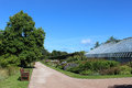Path and greenhouse st andrews botanic garden fife view along a in scotland with wooden bench seats on the grass at the side of Royalty Free Stock Photos