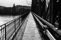 Path on industrial bridge leading to far away railroad and pedestrian black and white photo Royalty Free Stock Images