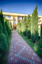 Path leading to hotel scenic view of paved pathway with or guest house in background Stock Photos