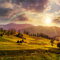 Path near field with haystacks at sunset composte landscape haystack on a green meadow in the mountains in light rainbow Royalty Free Stock Image