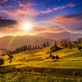 Path near field with haystacks at sunset composte landscape haystack on a green meadow in the mountains in light rainbow Royalty Free Stock Photo
