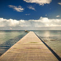 Path on the pier by the ocean with blue sky and clouds Royalty Free Stock Photo