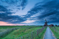 Path to windmill in clouded dusk groningen netherlands Royalty Free Stock Image