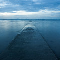 Pathway receding over blue sea scenic view of with cloudscape background Royalty Free Stock Photos