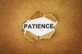 Patience the word in the hole of brown paper Royalty Free Stock Photos