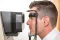 Patient and auto refractometer at optician or optometrist Royalty Free Stock Photo