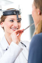 Patient in a examination by doctor in clinic young female or ent specialist with her practice examining the throat with spatula Stock Image