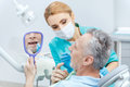 Patient looking at mirror while professional dentist checking teeth