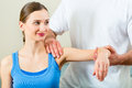 Patient at the physiotherapy doing physical therapy female exercises with her therapist he gives her a medical massage Stock Image