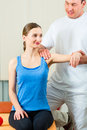 Patient at the physiotherapy doing physical therapy female exercises with her therapist he gives her a medical massage Royalty Free Stock Image