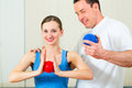 Patient at the physiotherapy doing physical therapy female exercises with her therapist they using a massage ball Royalty Free Stock Photo