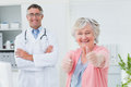 Patient showing thumbs up sign while standing with doctor portrait of happy female in clinic Stock Photography