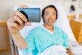Patient taking self portrait through mobile phone mature male in hospital Stock Photos