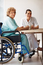 Patient on a wheelchair having coffee with a nurse Stock Photos