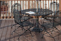 Patio bible a pair of reading glasses rests on top of an open on a wrought iron table on a wooden deck as the evening shadows Stock Photo
