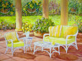 Patio with wicker furniture a surrounded by columns and flowering hanging baskets has white chairs and tables in an acrylic Stock Image