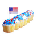Patriotic cupcakes decorated with american flag and blue white cream with red stars sprinkles on the top isolated Stock Photo