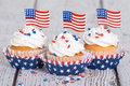 Patriotic cupcakes with sprinkles and american flags on vintage background Royalty Free Stock Photo